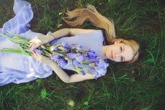 有金发碧眼的女人的可爱的女孩dren嗅到蓝色紫色虹膜花的头发和自然构成说谎在草户外, tendern 免版税图库摄影