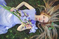 有金发碧眼的女人的可爱的女孩dren嗅到蓝色紫色虹膜花的头发和自然构成说谎在草户外, tendern 库存照片