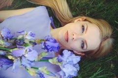有金发碧眼的女人的可爱的女孩dren嗅到蓝色紫色虹膜花的头发和自然构成说谎在草户外, tendern 库存图片
