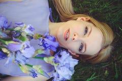 有金发碧眼的女人的可爱的女孩dren嗅到蓝色紫色虹膜花的头发和自然构成说谎在草户外, tendern 免版税库存照片