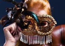 有金威尼斯式屏蔽的美丽的妇女 库存图片
