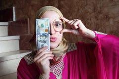 有金子和金钱的愉快的阿拉伯回教妇女 免版税库存照片