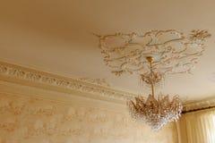 有金子的水晶枝形吊灯在与减速火箭的灰泥的一块白色天花板 库存照片