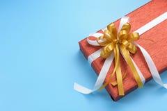 有金子的红色礼物盒和白色丝带在蓝色背景鞠躬 免版税图库摄影
