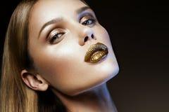 有金子闪烁的Beautyful女孩在她的面孔 免版税库存照片