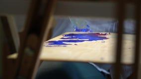 有金属小铲的女孩画家画的油漆的混和在调色板视图的油漆从画架的后面 股票录像