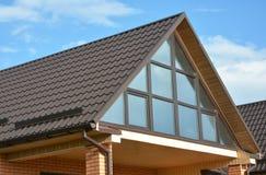 有金属屋顶、全景窗口、天窗、屋顶窗口和雨天沟系统的现代房子 免版税库存图片