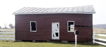 有金属屋顶的被毁坏的红色附属建筑 库存图片