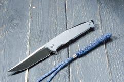 有金属把柄和一条蓝色短绳的刀子 前方 免版税库存图片