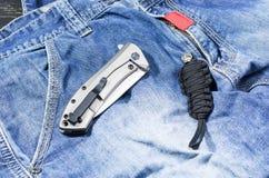 有金属把柄的刀子以被折叠的形式 牛仔布背景 paracord的链子 免版税库存图片
