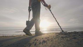 有金属探测器查寻珍宝的人在废墟中的海洋热带沙滩与他的在日出的狗 股票录像