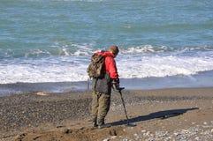 有金属探测器的人在海滩 库存图片