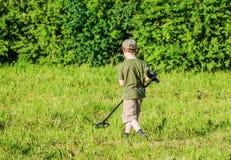 有金属探测器的男孩在一个绿色草甸 免版税库存照片