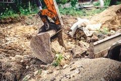 有金属桶移动的地球特写镜头的反向铲挖掘机在建造场所的 免版税库存图片