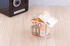 有金属硬币银行的钞票房子 免版税库存照片