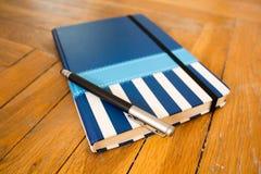 有金属笔的闭合的蓝色笔记本 免版税库存图片