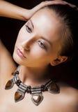 有金属项链和琥珀的可爱的妇女。 自然构成 免版税库存照片
