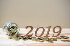 有金币堆的2019新年快乐和在桌上的木数字 事务,投资,退休计划,财务,挽救a 库存照片