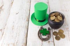 有金币的愉快的St Patricks天妖精帽子和在葡萄酒的幸运的魅力称呼白色木背景 顶视图 库存图片