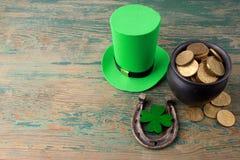 有金币的愉快的St Patricks天妖精帽子和在葡萄酒的幸运的魅力称呼绿色木背景 顶视图 免版税库存图片