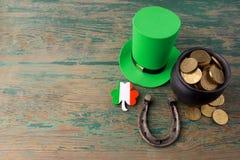 有金币的愉快的St Patricks天妖精帽子和在葡萄酒的幸运的魅力称呼绿色木背景 顶视图 免版税图库摄影