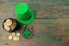 有金币的愉快的St Patricks天妖精帽子和在葡萄酒的幸运的魅力称呼绿色木背景 顶视图 免版税库存照片