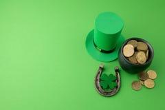 有金币的愉快的St Patricks天妖精帽子和在绿色背景的幸运的魅力 顶视图 免版税图库摄影