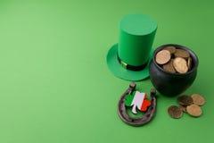 有金币的愉快的St Patricks天妖精帽子和在绿色背景的幸运的魅力 顶视图 免版税库存照片