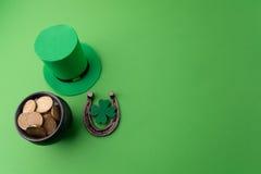 有金币的愉快的St Patricks天妖精帽子和在绿色背景的幸运的魅力 顶视图 免版税库存图片