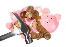 有金币的残破的被隔绝的存钱罐和锤子 免版税库存照片