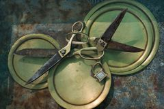 有金把柄的两把老古色古香的剪刀,被插入入彼此被在黄色铜盘的圆环,通信的标志, 图库摄影