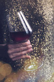有金拿着红葡萄酒的亮晶晶的小东西礼服的妇女玻璃 库存照片