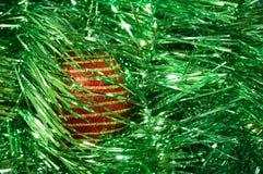 有金条纹的红色圣诞节玩具在一个绿色背景特写镜头 背景圣诞节新年度 免版税库存图片