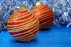 有金条纹的红色圣诞节玩具在一个蓝色背景特写镜头 背景圣诞节新年度 免版税库存图片