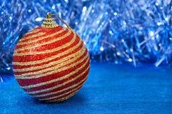 有金条纹的红色圣诞节玩具在一个蓝色背景特写镜头 背景圣诞节新年度 库存照片
