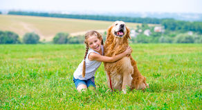 有金毛猎犬的小女孩 库存照片