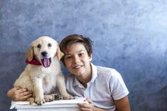 有金毛猎犬的青少年的男孩 图库摄影