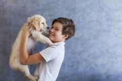 有金毛猎犬的青少年的男孩 库存照片