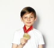 有金牌的逗人喜爱的白肤金发的男孩 免版税库存照片