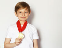 有金牌的逗人喜爱的白肤金发的男孩 库存图片