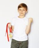 有金牌的逗人喜爱的白肤金发的男孩 免版税库存图片