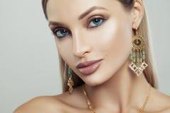 有金耳环的可爱的妇女有绿色宝石的 库存图片