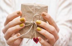 有金钉子设计的女性手 库存照片