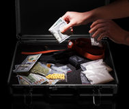 有金钱、枪和药物的手 图库摄影