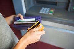 有金钱和信用卡的手在atm机器 库存图片