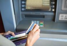 有金钱和信用卡的手在atm机器 免版税库存图片