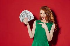 有金钱指向的年轻红头发人女孩 免版税库存照片