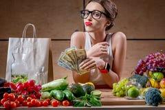 有金钱现金和健康食物的妇女 免版税库存图片
