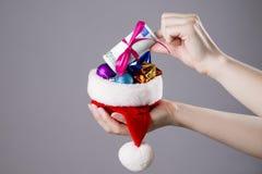 有金钱的圣诞老人帽子在妇女手上 库存图片