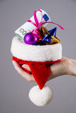 有金钱的圣诞老人帽子在妇女手上 免版税库存图片